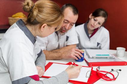 Pflegedokumentation .Drei Pfleger sitzen bei einer Besprechnung