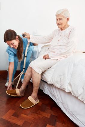 Pflegekraft bei der Hilfe beim anziehen